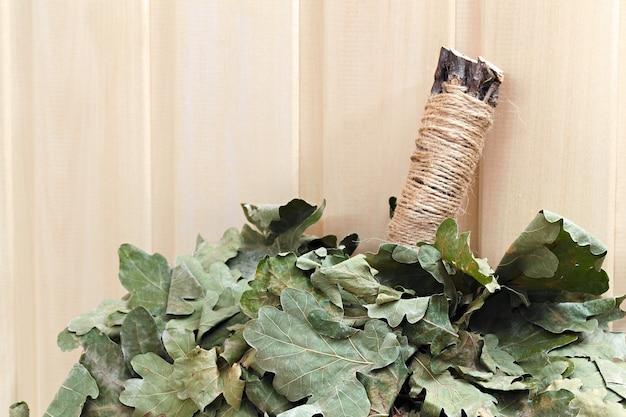 Из веток дубового веника для русской бани. на деревянной поверхности.