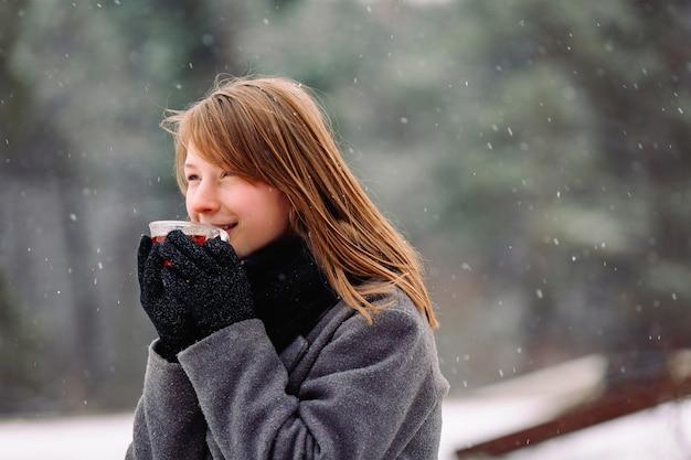 От холода замерзшая девушка держит чашку горячего чая, наслаждается ароматом и смотрит в сторону на
