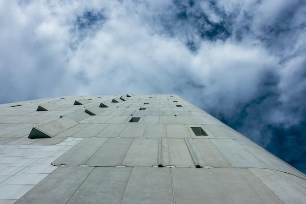 С точки зрения архитектуры небоскреб бизнес-офисное здание с голубым небом, корпоративное здание в городе.