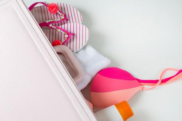 Из розового чемодана можно увидеть вещи для пляжа: солнцезащитный крем, купальник, полотенце, тапочки