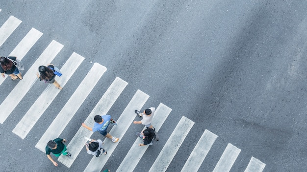 The from the top crosswise view of people walk on street pedestrian crossroad in the city street ,bird eye view.
