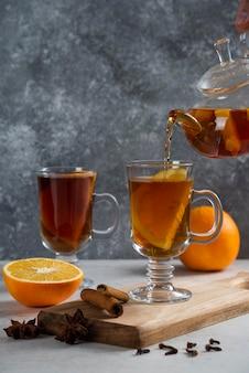 透明なガラスのティーポットから、ガラスのマグカップにお茶を注ぎます。
