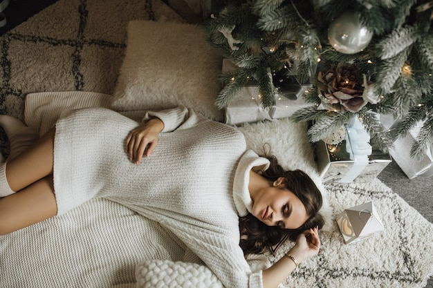 From above view, girl lies near a christmas tree with closed eyes