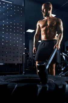 From above view of muscular caucasian man carrying big sledgehammer in hand.