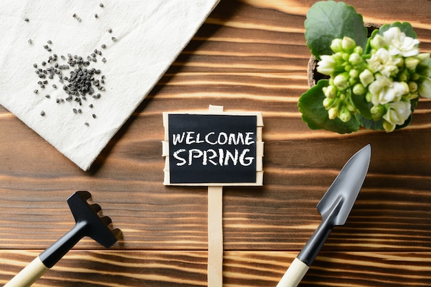 From above welcome spring sign and tools for gardening on wooden table