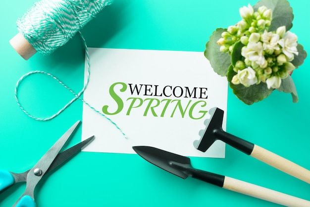 From above welcome spring words and different instruments for gardening on the turquoise table
