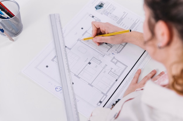 From above woman drawing blueprint