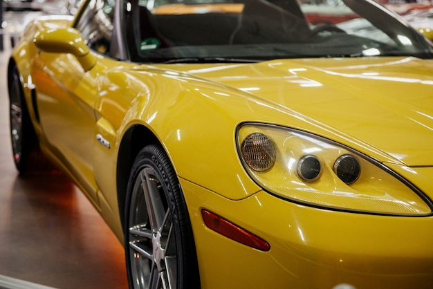 Передняя и правая сторона современного желтого автомобиля с неоновым светом и серебристым передним колесом