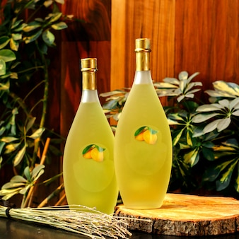 茶色の表面にあるガラス瓶の中のフロントアングルレモンジュース