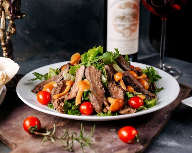 ブラウンデスクと暗い床に野菜と一緒に前アングル肉料理おいしいスライス肉
