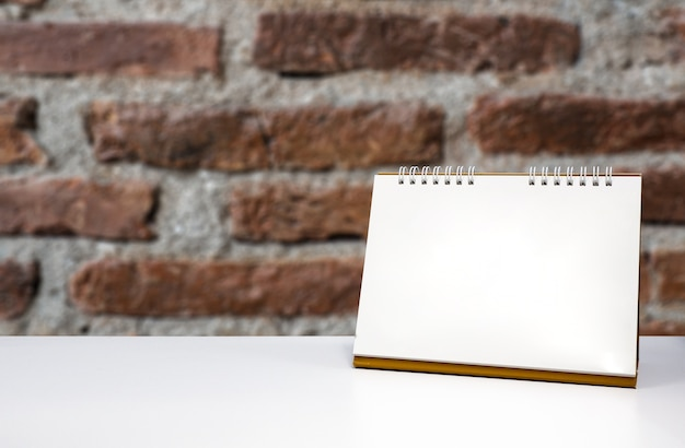 Front blank calendar on the desk in the office with old brick wall as background