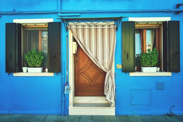 Front of the blue house on the island of burano. italy, venice. toned
