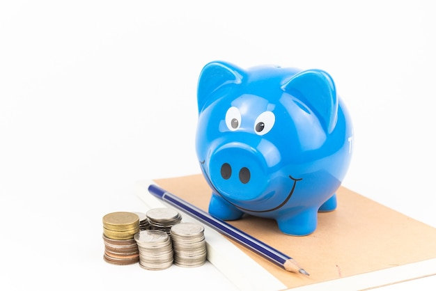 Front of blue piggy bank on the notebook with coins pile on white background