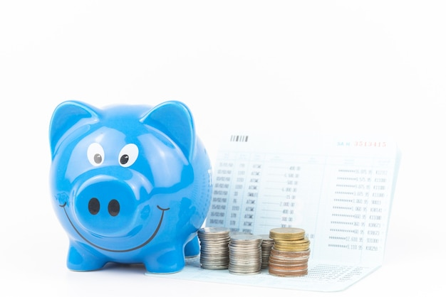 Front of blue piggy bank with coins pile on account book white background