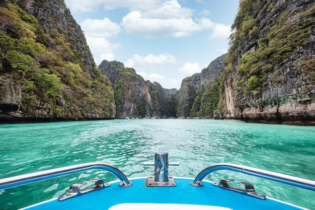 Front of boat sailing on pileh lagoon with cliff limestone of turquoise sea in phi phi island, thailand