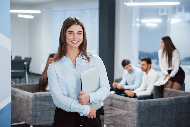 In front of business people. portrait of young girl stands in the office with employees at background