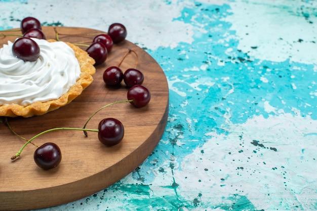 水色の机の上に隔離された新鮮なサワーチェリーとフロントクローズクリーミーケーキ、写真の色のケーキビスケットクリーム焼き