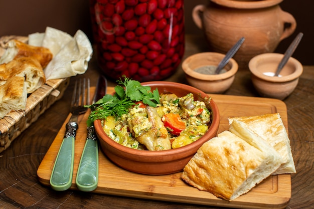 A front close up view cooked meal inside brown round pot along with bread slices