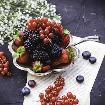 Front close up view fresh fruits multicolored fresh ripe fruits such as blackberries and red strawberries inside metal plate on the dark floor