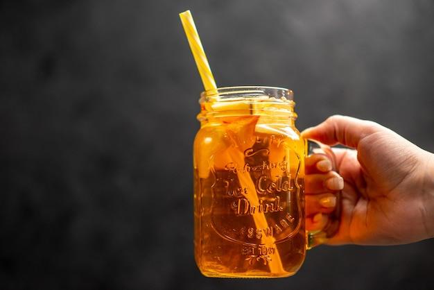 Vista ravvicinata frontale della mano che tiene un bicchiere di succo naturale e delizioso con un tubo in esso su sfondo nero