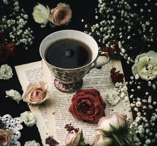 A front close up view hot tea on the paper and around colorful roses on the dark surface