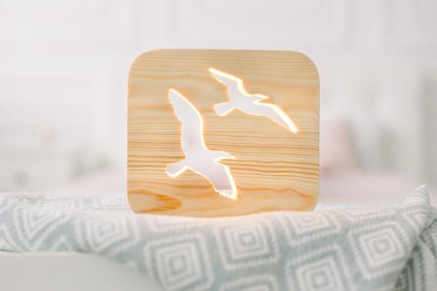 Вид спереди крупным планом стильной деревянной ночной лампы с изображением птиц, на сером одеяле в уютном светлом интерьере спальни.