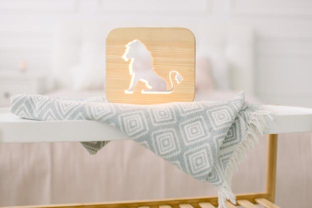 Вид спереди крупным планом стильной деревянной ночной лампы с вырезанным изображением льва на сером одеяле в уютном светлом интерьере спальни.