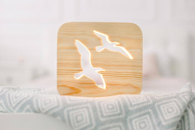 Front close up view of stylish wooden night lamp with birds picture, on gray blanket at cozy light bedroom interior.