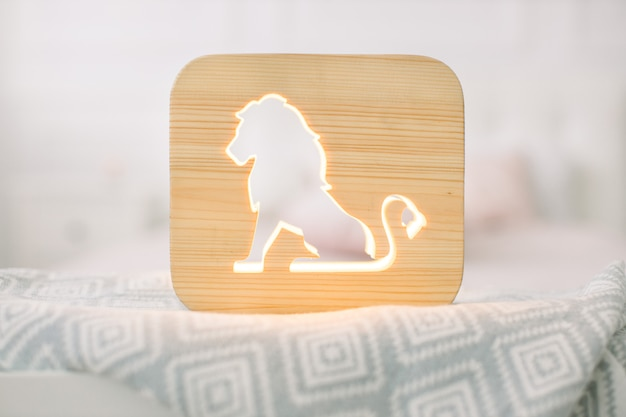 Front close up view of stylish wooden night lamp with lion cut out picture, on gray blanket at cozy light bedroom interior.