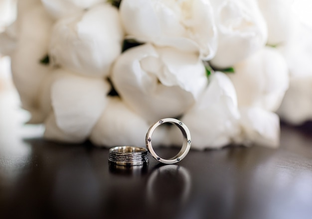Front close up view of two wedding rings lying on the peonies bouquet background
