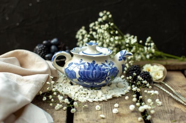 Un bollitore blu bianco bianco di vista alta di fine anteriore sul tessuto bianco sul pavimento rustico di legno