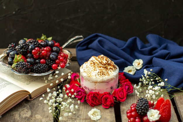 A front close up view yummy dessert around red roses and fresh berries on the brown wooden rustic desk