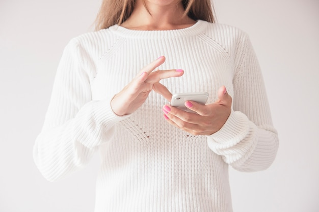 Front close up of woman using mobile smart phone, swiping up gesture