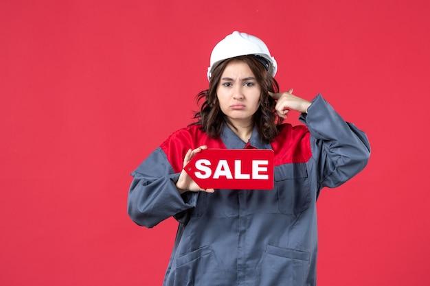 Vista frontale ravvicinata della lavoratrice aggressiva in uniforme che indossa elmetto che mostra l'icona di vendita sulla parete rossa isolata