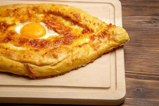 Vista ravvicinata anteriore pane al forno con uovo cotto sulla superficie in legno pane panino cibo uovo pasta per la colazione