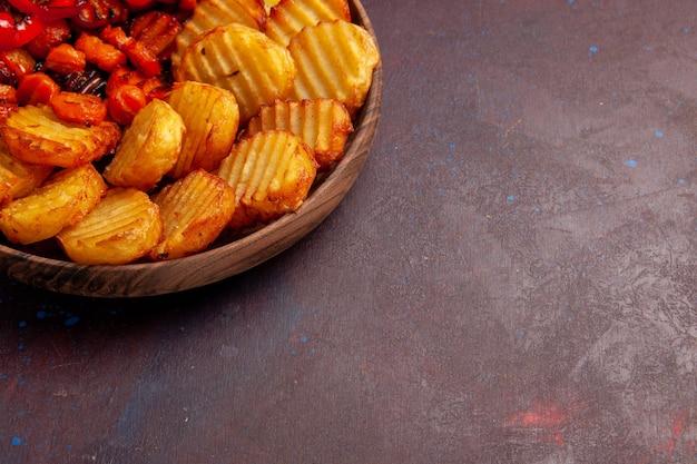 Patate al forno vista ravvicinata frontale con verdure cotte in uno spazio buio