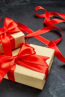 Vista frontale ravvicinata di bellissimi doni con nastro rosso su sfondo scuro