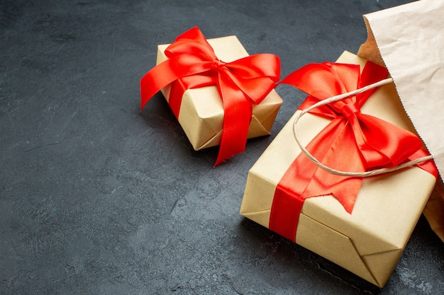 Vista frontale ravvicinata di bellissimi doni con nastro rosso su un tavolo scuro