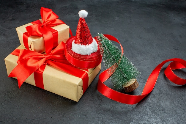 Front close view of beautiful gifts with red ribbon and santa claus hat christmas tree on dark table
