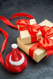 Vista frontale ravvicinata di bellissimi doni con nastro rosso e cappello di babbo natale su un tavolo scuro
