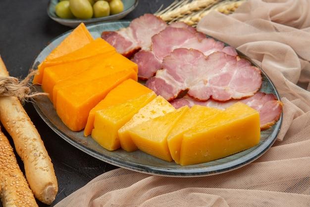 Vista frontale ravvicinata dei migliori snack deliziosi per il vino su un asciugamano su un tavolo scuro