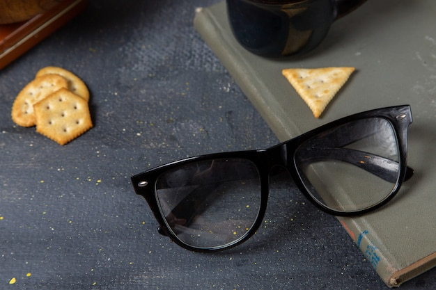 Front close view black sunglasses with crisps on the grey surface