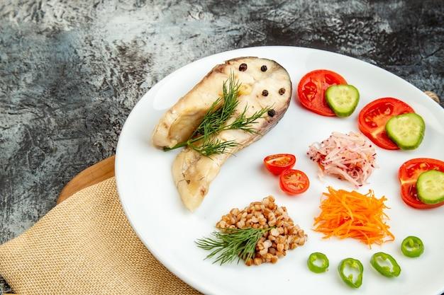 Vista ravvicinata frontale del pasto di grano saraceno di pesce bollito servito con verdure verdi su un piatto bianco su asciugamano nudo su tagliere di legno sulla superficie del ghiaccio