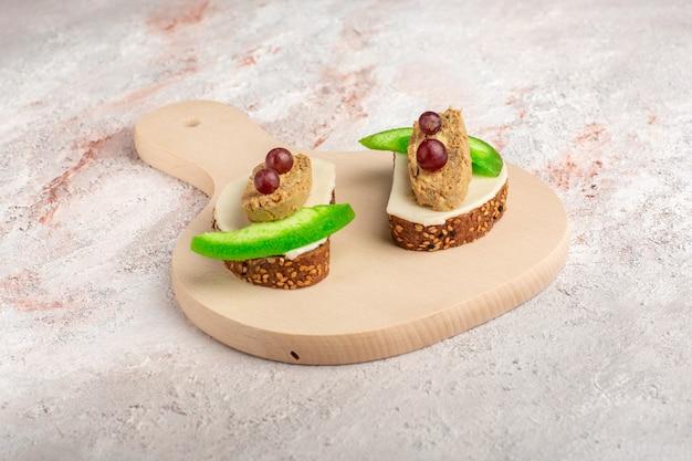Хлебные тосты с паштетом и ломтиками огурца внутри тарелки на белой поверхности