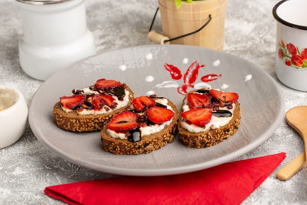 Front close view bread toasts with strawberries and sour cream inside plate on grey