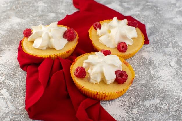 Фронтальный торт с кремовым вкусом и малиной на серой поверхности