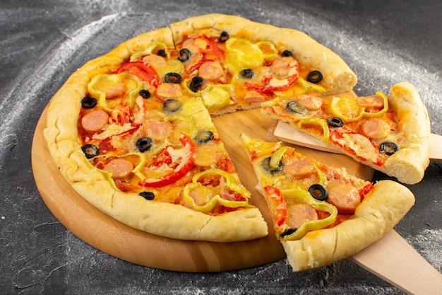暗い机の上の赤いトマト、ブラックオリーブ、ベルペッパー、ソーセージの正面の近くのチーズのピザ