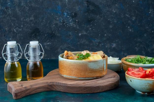 正面から見たチキンスープ、ジャガイモ、塩コショウの新鮮な野菜、紺色のデスクスープ肉料理の食事