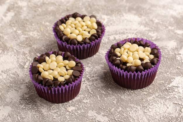 Vista frontale vicino gocce di cioccolato bianco e scuro all'interno di carte viola sulla superficie della luce
