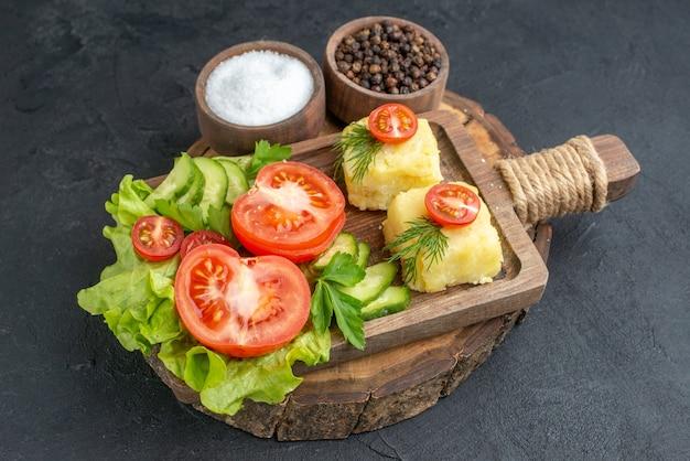 Vista frontale ravvicinata del formaggio di verdure fresche tritate e intere su tagliere e spezie su superficie nera